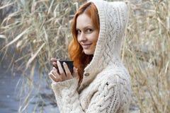 温暖的毛线衣的少妇喝一个杯子热的饮料的 免版税库存图片
