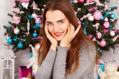 温暖的毛线衣的年轻愉快的妇女在与prese的新年树附近 库存图片