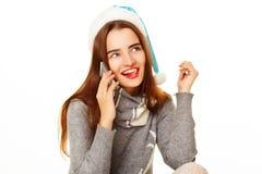 温暖的毛线衣的年轻愉快的妇女谈话在whi的电话 图库摄影