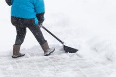 温暖的水兵的老妇人清除与雪铁锹的随风飘飞的雪 免版税库存照片