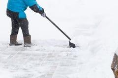 温暖的水兵的老妇人清除与雪铁锹的随风飘飞的雪 库存图片