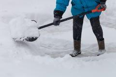 温暖的水兵的老妇人清除与雪铁锹的随风飘飞的雪 免版税库存图片