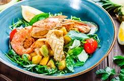 温暖的沙拉用海鲜,海螯虾,淡菜,虾,乌贼,扇贝,芒果,菠萝,鲕梨 免版税库存图片
