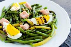 温暖的沙拉用煮熟的青豆、金枪鱼和煮沸的鸡蛋 免版税库存照片