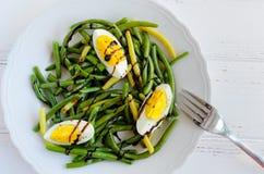 温暖的沙拉用煮熟的青豆和煮沸的鸡蛋 免版税库存图片
