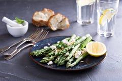 温暖的沙拉用芦笋、希腊白软干酪和柠檬 库存照片