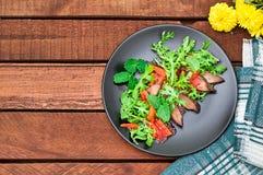 温暖的沙拉,与芝麻菜,鲜美,时兴的食物,新的盘服务的鸭子 背景土气木 顶视图 图库摄影
