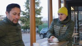 温暖的泡影夹克的两位男性运动员在训练谈话在咖啡馆的室外区域以后在晚上 人 股票录像