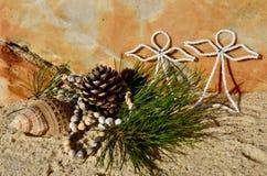 温暖的海滩圣诞节杉木锥体白色串珠的天使在7月使沙子和壳圣诞节靠岸 库存图片