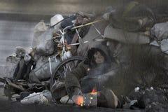 温暖的火给无家可归者带来希望在冷的冬天 免版税库存照片
