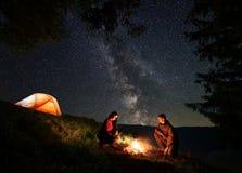 温暖的男性和女性在火附近在野营在满天星斗的天空上的晚上 库存图片