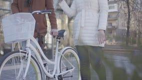 温暖的白色棕色外套的走在有自行车的街道上的夹克和高人的无法认出的妇女 休闲  影视素材