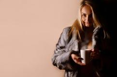 温暖的礼服的女孩有咖啡杯的 免版税库存照片