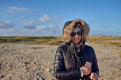 温暖的秋天成套装备的时髦妇女有太阳镜的 免版税库存图片
