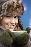 温暖的穿戴的饮用的女孩俏丽的微笑&# 免版税库存图片