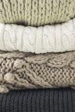 温暖的羊毛被编织的冬天和秋天衣裳,折叠在堆 毛线衣,围巾 特写镜头 免版税库存照片