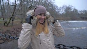 温暖的衣物微笑的站立的妇女在河的吊桥 股票视频