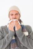 温暖的衣物的打喷嚏年轻的人 免版税图库摄影