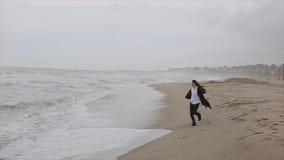 温暖的衣裳的一个美丽的女孩沿海滨跑 海的看法有泡沫似的波浪的在一个大风天 股票录像