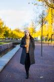 温暖的衣裳的可爱的妇女走在秋天公园的 免版税库存图片