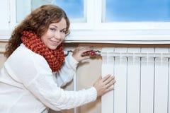 温暖的衣裳的妇女检查温度热化幅射器的在屋子里 免版税库存图片