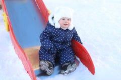 温暖的衣裳的小可爱的女婴室外在冬天 库存图片
