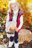 温暖的衣裳的小女孩用玩具兔子 库存图片