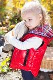 温暖的衣裳的小女孩用玩具兔子 免版税库存图片