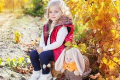 温暖的衣裳的小女孩用玩具兔子 免版税库存照片