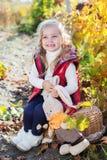 温暖的衣裳的小女孩用玩具兔子 库存照片