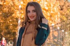 温暖的围巾的迷人的女孩在树中站立在公园并且微笑 免版税库存照片