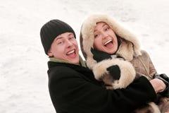 温暖礼服拥抱的女孩笑的人 免版税库存图片