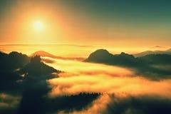 温暖红色五颜六色的蒸气的有薄雾的秋天土地 充分岩石谷大雾 太阳在五颜六色的薄雾掩藏 图库摄影