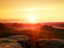 温暖红色五颜六色的阴影的有薄雾的秋天土地 充分岩石谷紫色雾和太阳在薄雾掩藏 库存照片