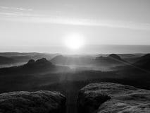 温暖红色五颜六色的阴影的有薄雾的秋天土地 充分岩石谷紫色雾和太阳在薄雾掩藏 库存图片