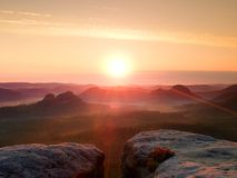 温暖红色五颜六色的阴影的有薄雾的秋天土地 充分岩石谷紫色雾和太阳在薄雾掩藏 免版税库存照片