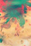 温暖红色抽象的背景,黄色,橙色墨水斑点swith绿色下落 免版税库存照片