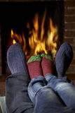 温暖脚的父亲和儿童佩带的袜子由火 免版税图库摄影