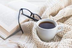 温暖被编织的格子花呢披肩、玻璃、杯子热的咖啡和书 图库摄影
