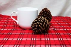 温暖饮料、白色杯子和杉木锥体在红色桌布前面fo 免版税库存图片