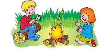 温暖他们的手的男孩和女孩由营火 库存照片