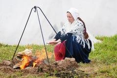 温暖他的手的Reenactor妇女由火 免版税图库摄影