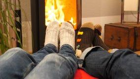 温暖他们的脚的两个人由壁炉 股票录像