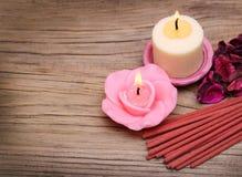 温泉。与干玫瑰叶子和香火棍子的灼烧的蜡烛 库存图片