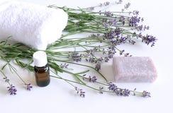 温泉与毛巾、芳香油、自然肥皂和淡紫色花的治疗和按摩产品在白色背景 免版税库存图片