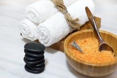 温泉做法的准备-在一把木碗的橙色腌制槽用食盐和匙子,三块白色毛巾在一个木箱和黑热 免版税库存照片