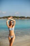 温泉健康海滩放松和日光浴在蓝色盐水湖附近的比基尼泳装游泳衣的秀丽妇女 美丽的平安的年轻人 免版税库存图片