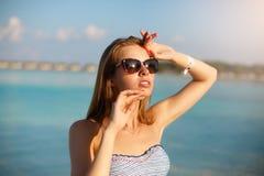 温泉健康海滩放松和日光浴在蓝色盐水湖附近的比基尼泳装游泳衣的秀丽妇女 美丽的平安的年轻人 库存图片