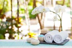 温泉和健康按摩设置静物画有蜡烛、毛巾和石头室外夏天背景 库存图片
