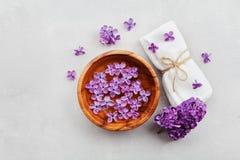 温泉和健康构成与充满香气的丁香开花水在木碗和毛巾在石背景,顶视图,平展位置 免版税库存照片